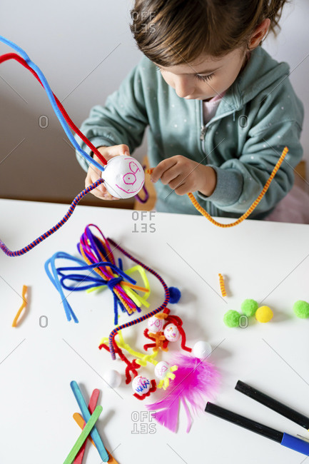 Cute girl making toys of styrofoam ball and pipe cleaners while sitting at table in living room
