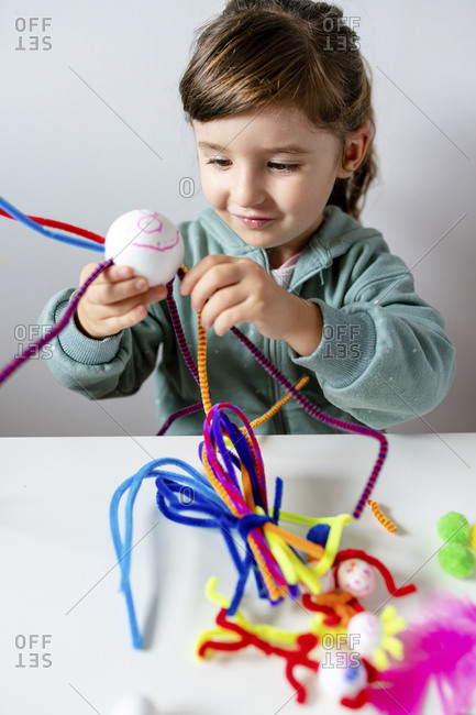 Smiling girl making toys of styrofoam ball and pipe cleaners while sitting at home