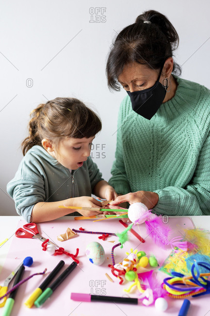 Grandmother and granddaughter making creative toys from pipe cleaners and pom-pom at home during pandemic