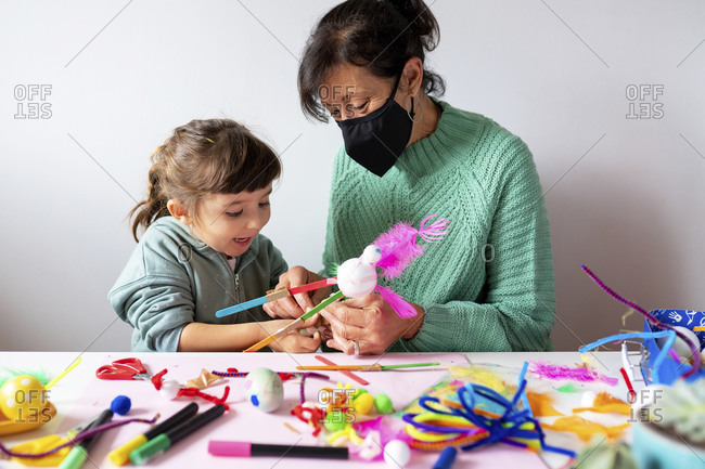 Grandmother and granddaughter making creative toys from pipe cleaners and pom-pom during COVID-19