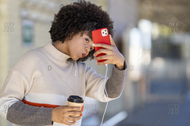 Young woman holding reusable cup making face while taking selfie from smart phone at railroad station