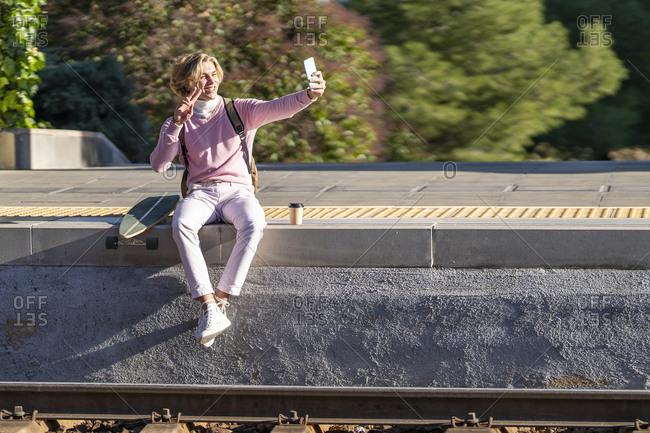 Smiling man gesturing peace sign while taking selfie sitting with longboard on station platform