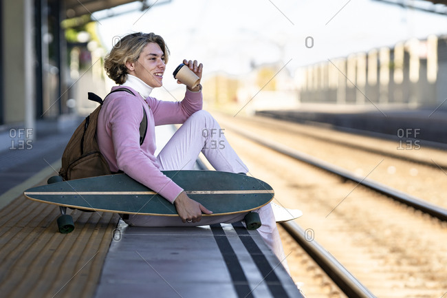 Smiling young man holding reusable cup while sitting with longboard at edge of railroad platform