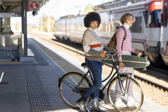 Smiling male and female friends looking away waiting with bicycle and longboard at railroad station