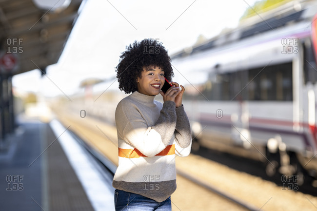Happy woman talking on mobile phone while waiting at railroad station