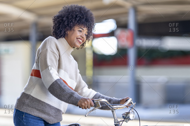 Smiling young woman with bicycle waiting at station