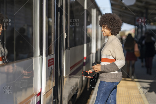 Happy young female passenger boarding train at station on sunny day