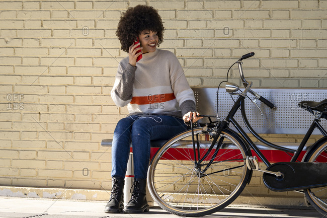 Happy female passenger talking through mobile phone while sitting on bench by bicycle against brick wall
