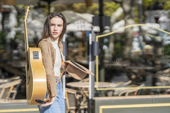 Contemplating female musician with guitar during sunny day