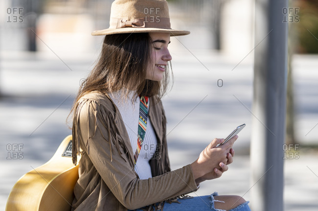 Young woman with guitar smiling while text messaging on smart phone during sunny day