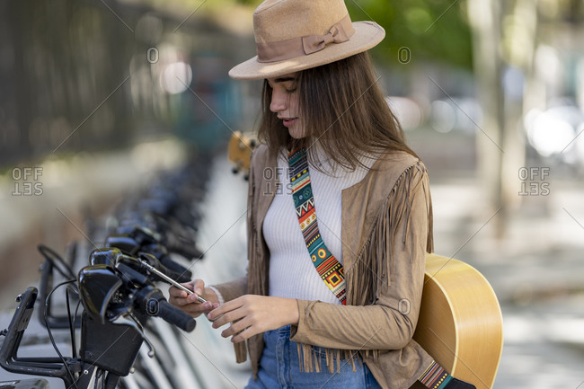 Young woman paying through smart phone at bicycle parking station