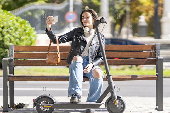 Smiling woman taking selfie through smart phone while sitting on bench by electric push scooter