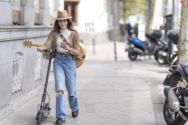 Young woman with electric push scooter using smart phone while walking on footpath in city