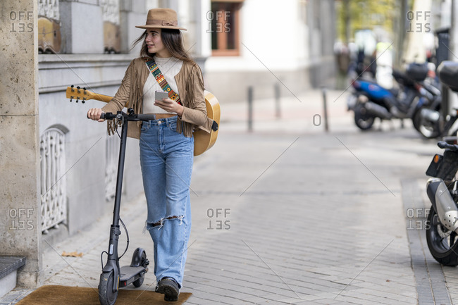 Female musician with electric push scooter holding smart phone while walking on footpath in city