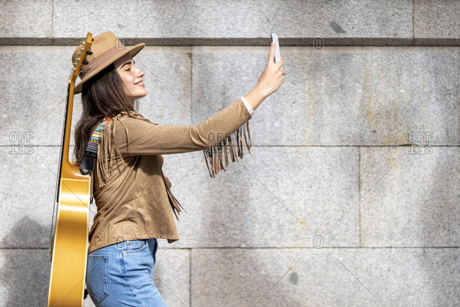 Young female musician taking selfie while walking by wall
