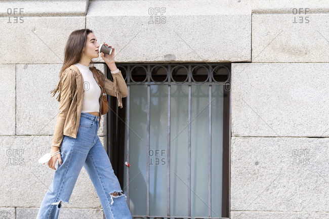 Young woman drinking coffee while walking by wall