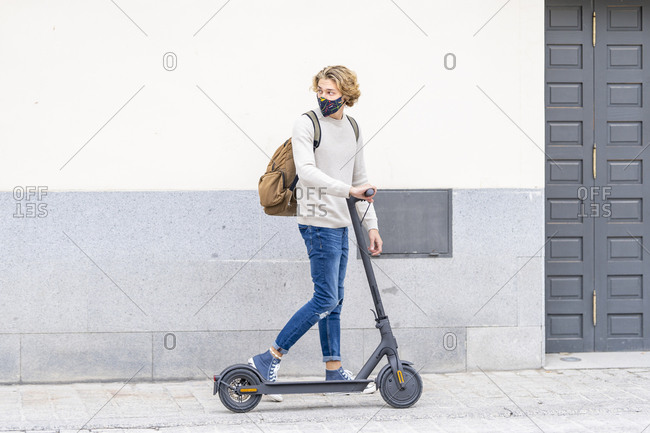 Young man wearing protective face mask standing with electric push scooter on footpath