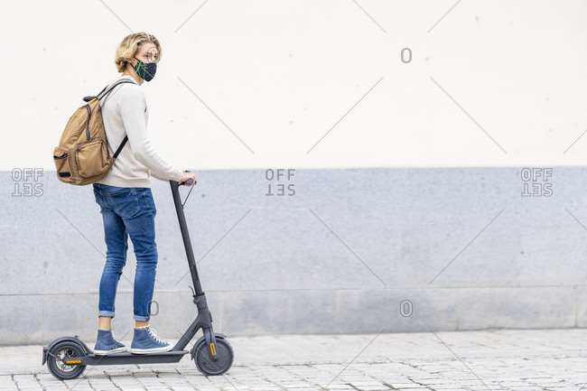 Man with face mask and backpack riding electric push scooter on footpath