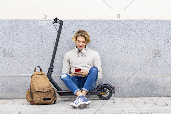 Smiling man with backpack using smart phone while sitting on electric push scooter