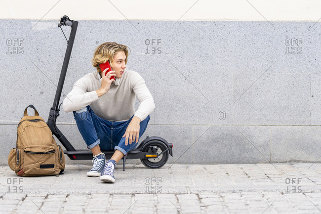 Man with backpack talking on mobile phone while sitting on electric push scooter against wall