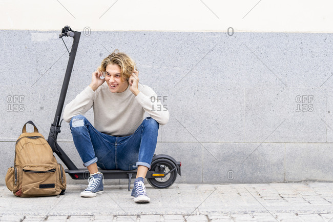 Smiling man with backpack wearing headphones while sitting on electric push scooter against wall