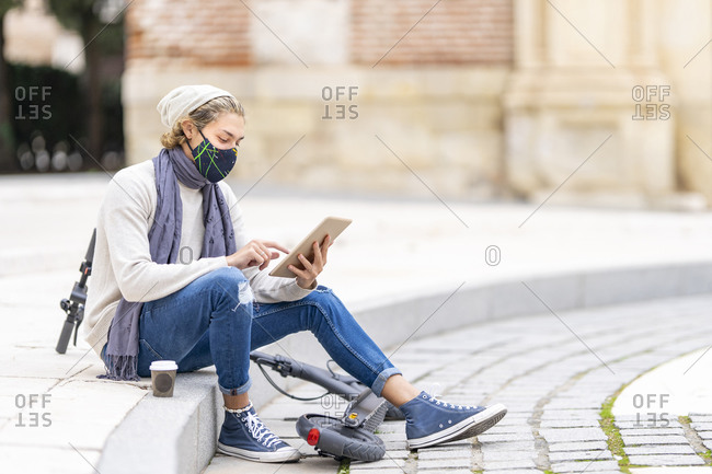 Young man with electric push scooter and face mask using digital tablet while sitting on footpath in city