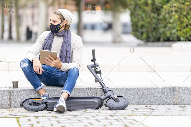 Man with electric push scooter and face mask using digital tablet while sitting on footpath in city