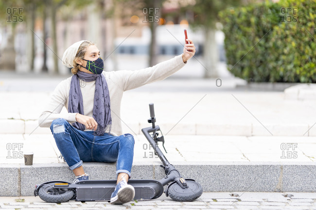 Man wearing face mask taking selfie through mobile phone while sitting with electric push scooter on footpath