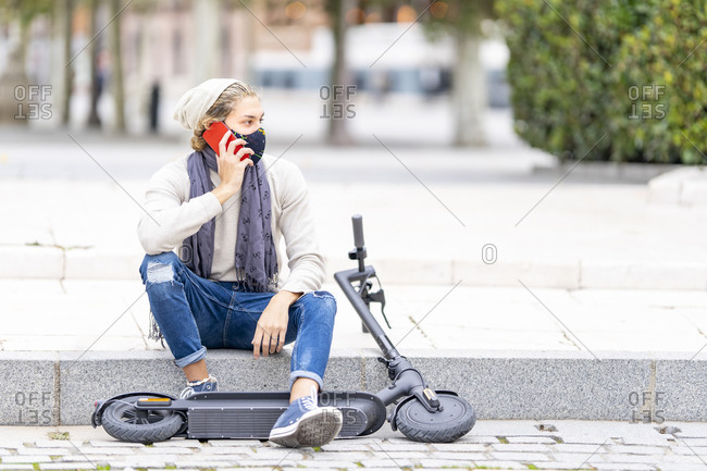 Young man wearing face mask talking on mobile phone while sitting with electric push scooter in city