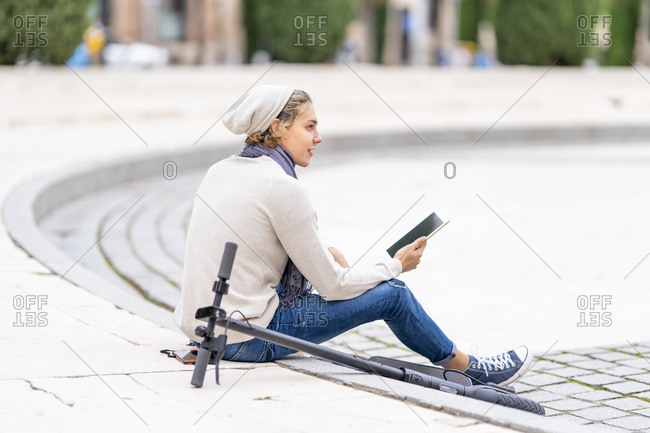 Man with knit hat using digital tablet while sitting by electric push scooter in city