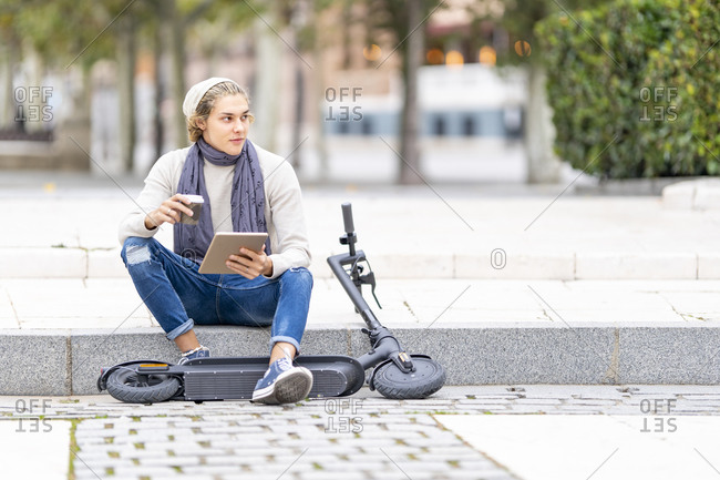 Man with electric push scooter using digital tablet while sitting on footpath