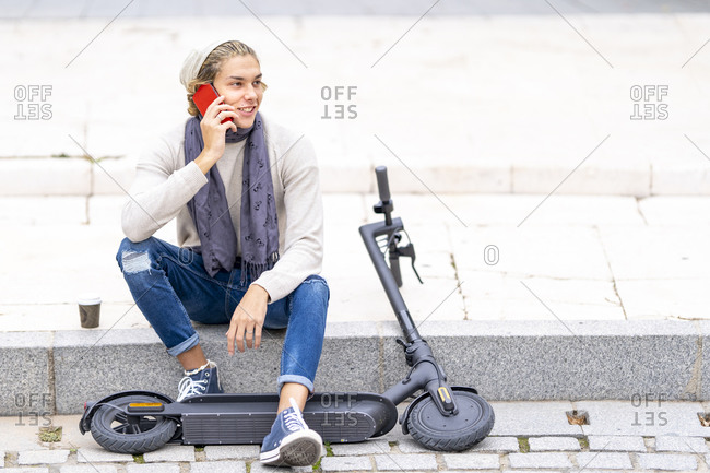 Young man talking on mobile phone while sitting by electric push scooter on footpath