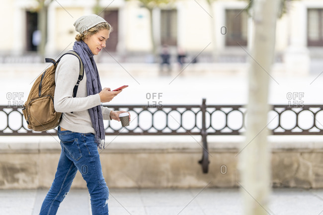 Young man with disposable cup using mobile phone while walking in city