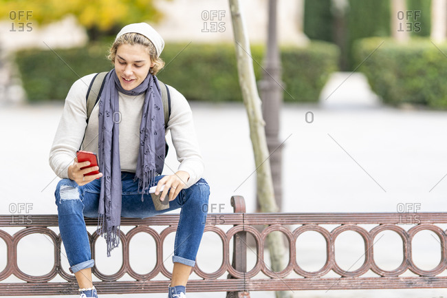 Smiling man with coffee cup using mobile phone while sitting on railing in city