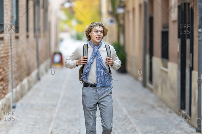 Young man wearing scarf looking away while walking on footpath