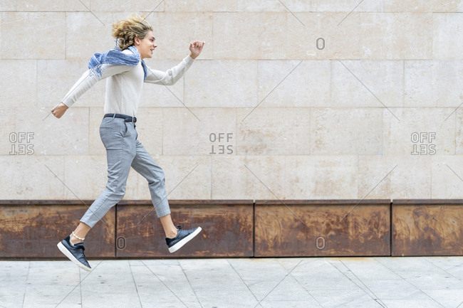 Carefree man walking on footpath against wall