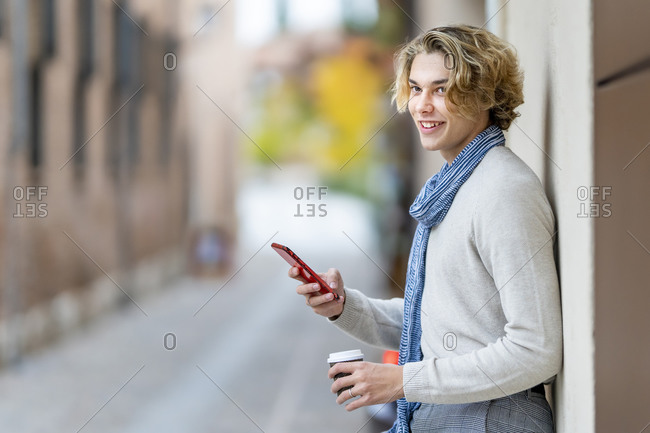 Smiling man with disposable cup using mobile phone while leaning on wall