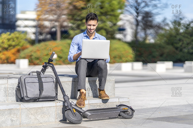 Businessman working on laptop while sitting by briefcase and electric push scooter in city