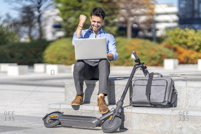 Smiling businessman showing winning gesture while sitting by briefcase and electric push scooter in city