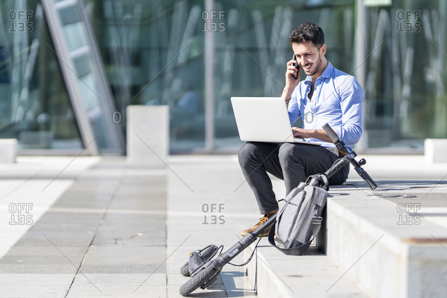Smiling businessman with laptop talking on mobile phone while sitting by briefcase and electric push scooter on steps