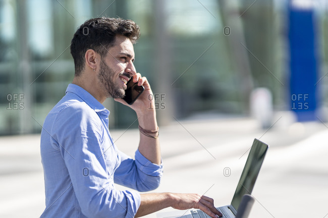 Businessman with laptop talking on mobile phone while working outdoors