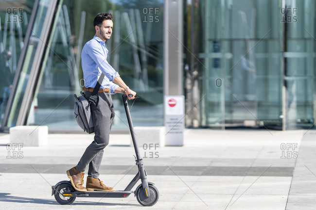 Young businessman with crossbody bag riding electric push scooter on footpath
