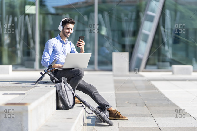 Businessman wearing headphones using mobile phone while sitting with laptop by electric push scooter and briefcase on steps