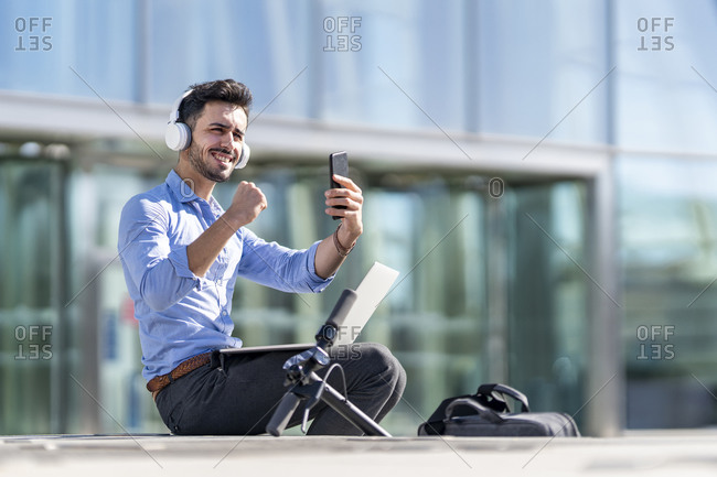 Smiling businessman wearing headphones showing winning gesture while sitting with laptop and mobile phone outdoors