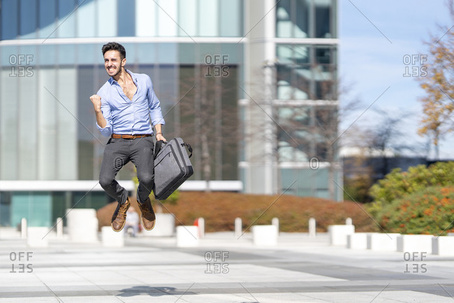 Excited businessman holding briefcase while jumping on footpath