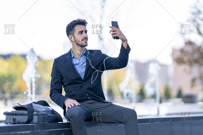 Businessman wearing in-ear headphones taking selfie through mobile phone while sitting on bench