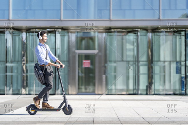 Young businessman wearing headphones riding push scooter on footpath