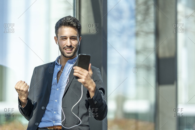 Smiling businessman wearing in-ear headphones cheering while using mobile phone standing outdoors