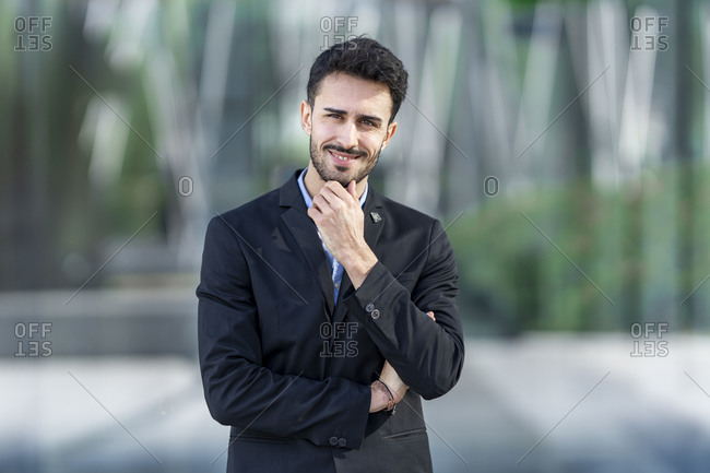 Young confident businessman with hand on chin smiling while standing outdoors