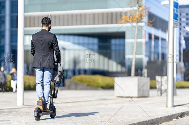 Businessman riding push scooter on footpath